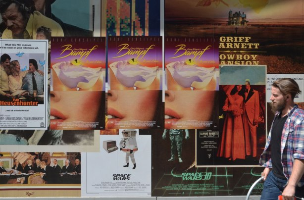 detail of an art installation that is a wall of fake movie posters