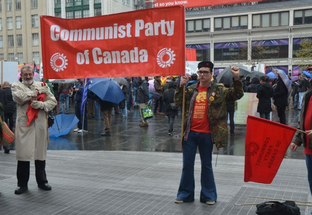 An older man holds one end of a red banner for the Communist Party of Canada while a young man holds the other end - May day, International Workers Day rally at Dundas Square on a rainy day -