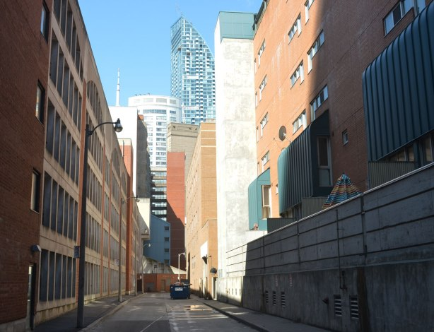 a downtown Toronto lane, very clean, no graffiti, taller, newer buildings on either side of the lane. CN tower in the distance,