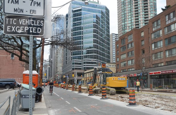 A digger and other equipment working on a torn up section of Bay street.