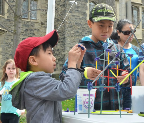 Two young Asian boys are building small structures with the building toy k'nex.
