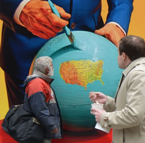 a man stands in front of a picture that is a large globe with everything painted light blue except the USA