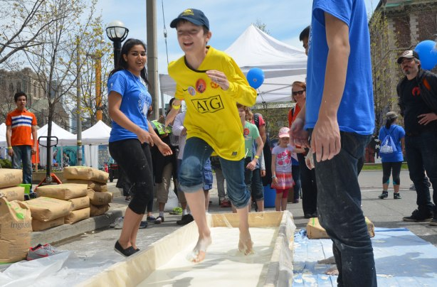 A boy is running barefoot along a course that is filled with corn starch and water. Onlookers are cheering him on.