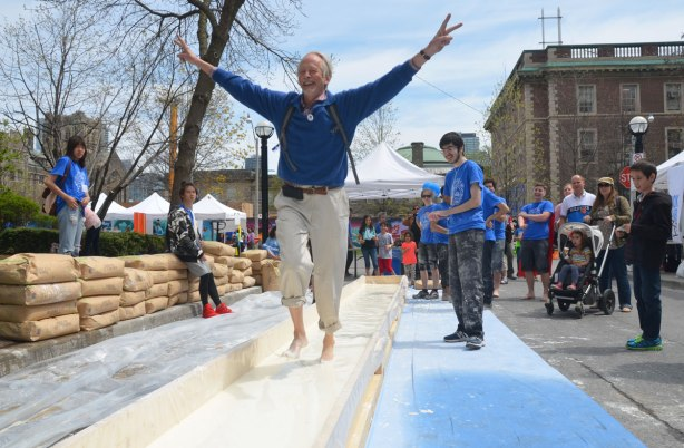 An older man is running through corn starch and water with his arms held up