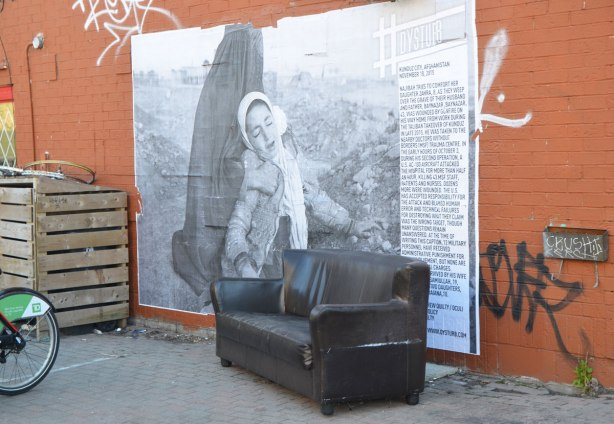 a large black and white photojournalist picture, part of CONTACT photography festival, pasted on a wall - a mother (covered in a black burka) and her daughter in grief, at a gravesite.  Pasted on an orange wall with an old brown leather sofa in front of it.