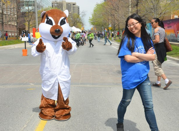 A person dressed in a costume that looks like an animal - squirrel? fox? that is wearing a lab coat. An Asian woman who was walking with him before the photo was taken is shyly turning away, she is also laughing