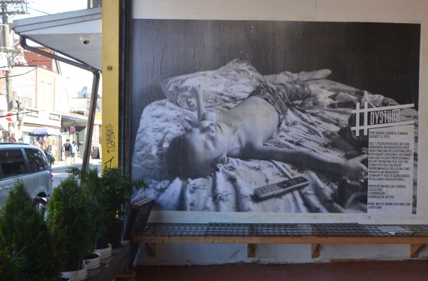 a large black and white photojournalist picture, part of CONTACT photography festival, pasted on a wall - a sick boy is lying on a bed, on a wall in the entranceway to a store, sidewalk and street scene in the background