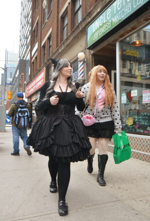 two women dressed up and walking down the street. One is in a puffy black dress, black tights and black shoes. The other woman has long red hair and a polka dot sweater on.