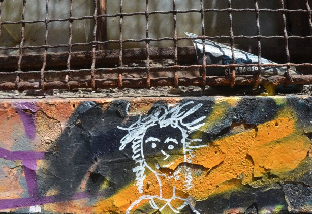 under the rusted metal of a wire grill over a window, on a wall that was painted in black and orange street art, there is a small white line drawing of a girl's head