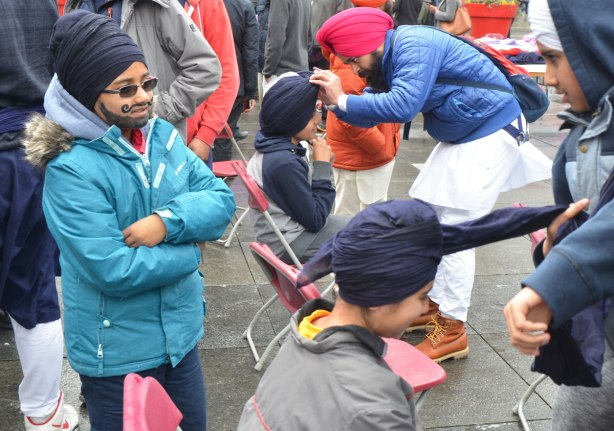 People having their heads wrapped in a turban, many different colours, at an event at Yonge Dundas square run by the Sikh Youth Federation. Sikh volunteers are making the turbans using stacks of fabric laid out on 5 long tables. A boy with a black turban and his face painted with a black beard and mustache watches others get turbans