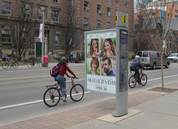 cyclists ride by an information pillar that has a large ad jutting out towards the street.