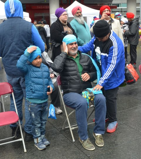 People having their heads wrapped in a turban, many different colours, at an event at Yonge Dundas square run by the Sikh Youth Federation. Sikh volunteers are making the turbans using stacks of fabric laid out on 5 long tables. A father and son with matching light blue turbans