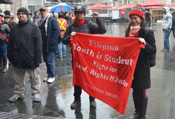 Two students hold a red banner for the Filipino Youth and Students fight for land, rights and justice - May day, International Workers Day rally at Dundas Square on a rainy day -