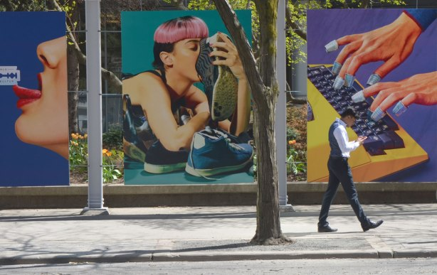 A man walks past large posters on King St.,