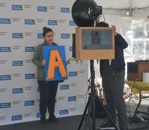 A young woman has her picture taken with a large orange letter A on a blue square.