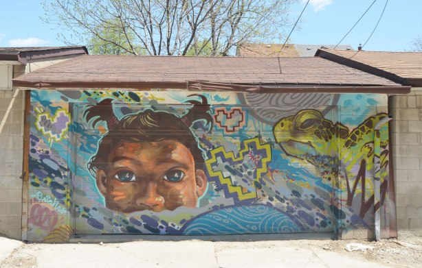 street art mural on a wall in an alley, a girls face, two little brown pigtails, 2 hearts and a turtle head