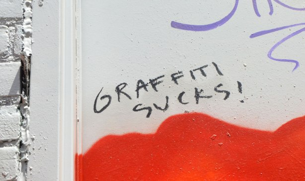 "graffiti wods on a red and white wall, ""Graffiti Sucks"""