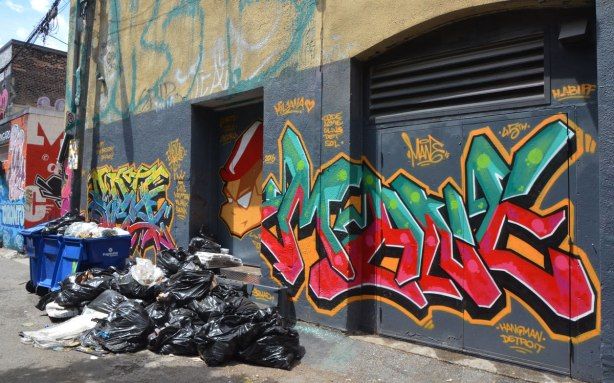 a bin of garbage plus a pile of garbage bags in front of a street art piece, a face and a tag in green and red, signed hangman, detroit.
