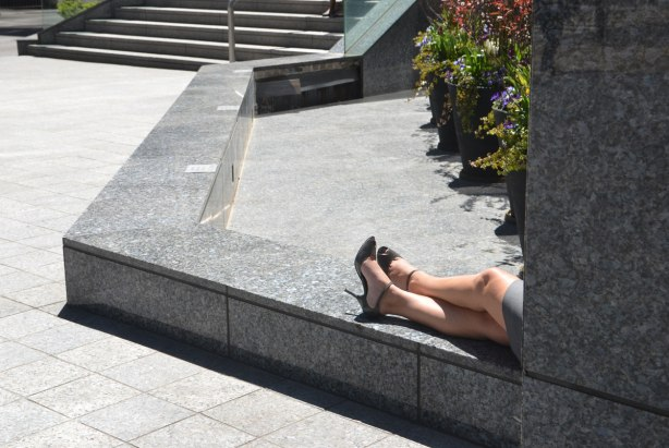 A woman in black high heel shoes is sitting on a low stone wall outside. You can only see her from the thigh down. He legs are crossed at the ankle.