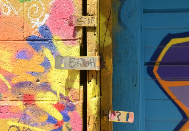 Three hinges have been bent forward so they are flat, multicoloured graffiti behind them, words written on the hinges except for the bottom one which has a question mark on it.