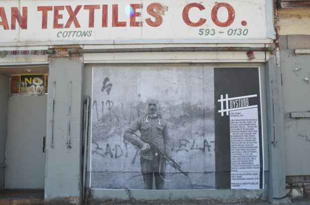 large black and white photo pasted onto a boarded up storefront of European Textiles on Spadina Rd. The photo is part of #Dysturb exhibit at Contact Photography Festival. It shows a hooded man holding an automatic rifle