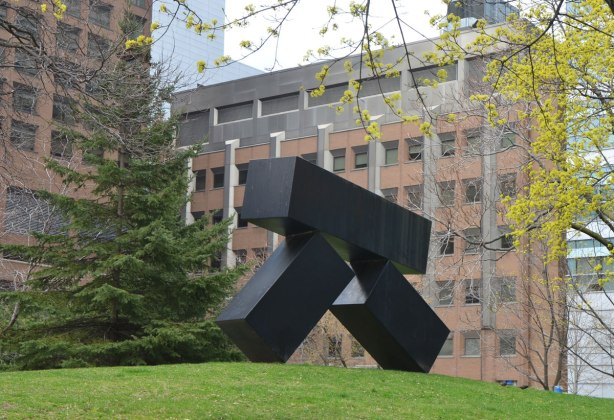 black metal sculpture of three boxes precariously balanced, the upper box is almost horizontal and it is being supported by the other two who are falling down but still balancing