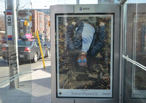an iphone ad on a bus stop wall of a man lying on the ground. He is upside down in the picture