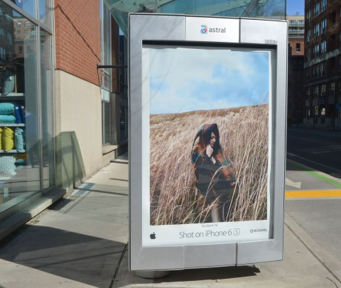 iphone ad on a bus stop wall showing a woman in a field