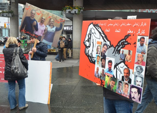 A man holds up a sign written in Arabic about men missing I think. It is red with a picture of a fist on it. On the fist are glued pictures of 16 men . Also in the picture, a man holding a placard with a photo of three men on it, talks to a woman whose back is to the camera.