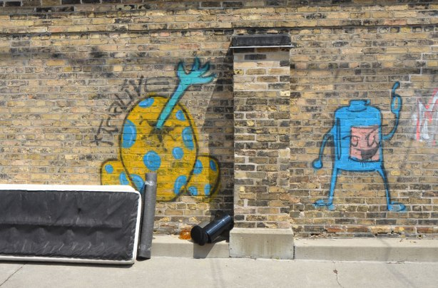 "an old mattress leans against an old brick wall that has two pieces of graffiti on it. One is a blue and yellow egg shape with a blue arm and hand sticking out of a crack in it. The words ""It's alive"" are written beside it. The other is a small blue creature like shape"