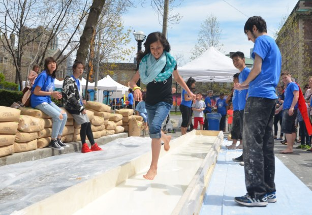 A girl is running barefoot along a course that is filled with corn starch and water. Onlookers are cheering him on.