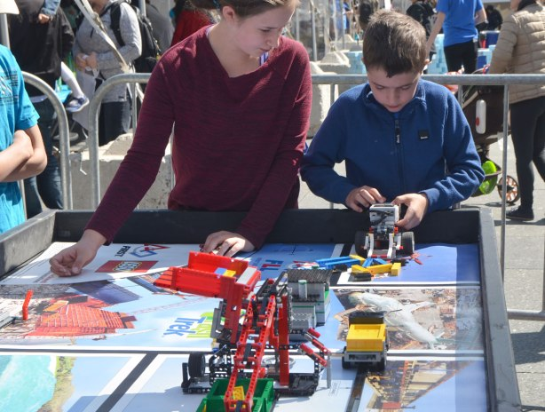 Two kids are playing with a programmable Lego car.