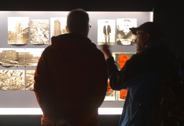 silhouette of two men standing in front of a lit display case of old photographs