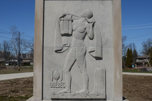Quebec sculpture - A stone relief sculpture from a series on provinces of Canada, originally on a Bank of Montreal building in Toronto. They were rescued when the bank was demolished and moved to the grounds of the Guild Inn in Scarborough. By Canadian artist Frances Loring. A naked woman upright, with a cloth over her shoulders and looking upwards