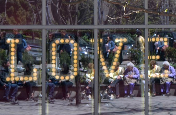 the word love is written in lights in capital letters in a window of a store. Reflected in the window is a group of older people sitting on benches across from the window
