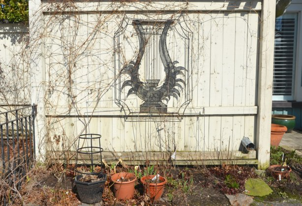 A small white fence with some empty planters in front of it. Old vines are on it (no leaves). There is a frame for plants to cling to in the shape of a lyre that is attached to the fence