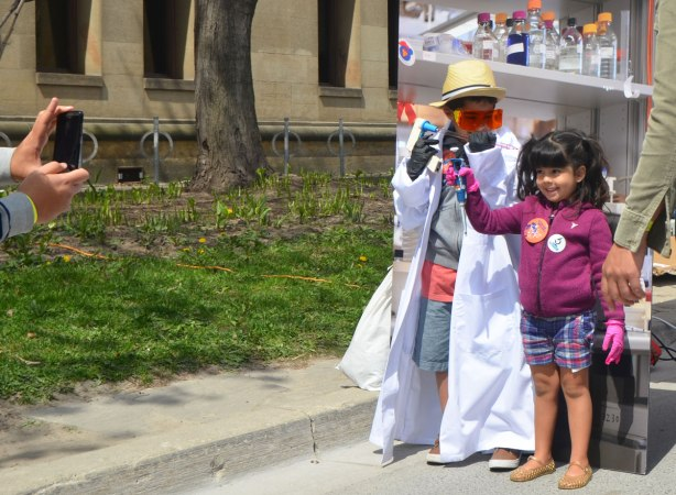 Two young kids have been dressed up as mad scientists and their father is taking their picture. They had rubber gloves on, eye protection and a lab coat. They both have pipettes.