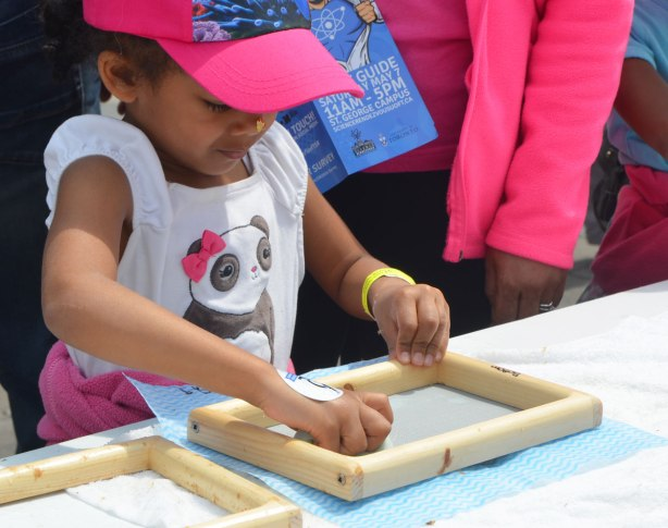 a young girl is making paper. she is sponging the paper dry over a piece of mesh in a frame