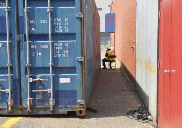 a man sits on a chair between a blue shipping containter and a building,