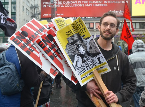 A young man is giving out placards at a rally - May day, International Workers Day rally at Dundas Square on a rainy day -