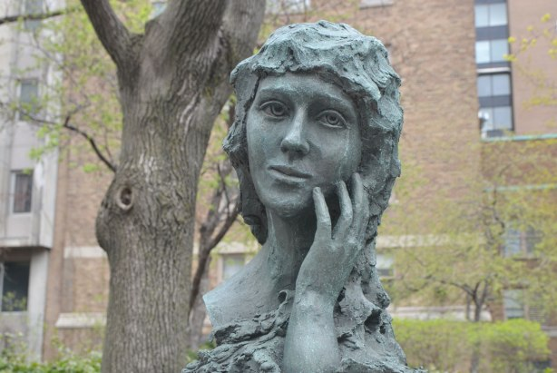 bust of Mary Pickford with her hand on her cheek, in front of Sick Kids Hospital in Toronto, red brick hospital behind her in the photo