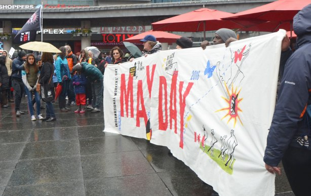 A group of women standing behind and holding up a large white banner for May Day - May day, International Workers Day rally at Dundas Square on a rainy day -