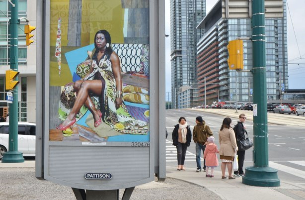 part of an art installation, portrait of a black woman on a billboard, by Mickalene Thomas, in a parking lot in downtown Toronto, A group of people wait for a green light at the intersection in the background, tall condos too.