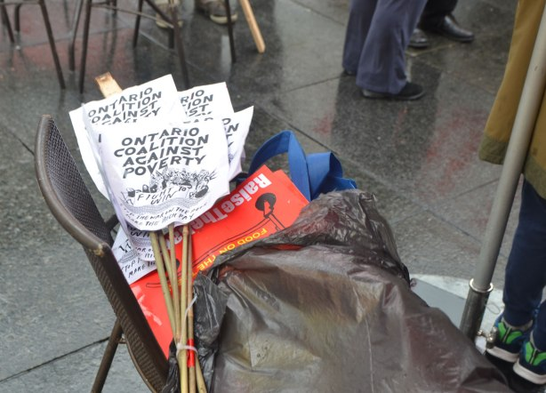 a bundle of small OCAP placard signs sit on a chair - May day, International Workers Day rally at Dundas Square on a rainy day -