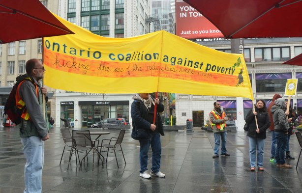 Three people hold a large yellow banner for the Ontario Coalition Against Poverty - May day, International Workers Day rally at Dundas Square on a rainy day -