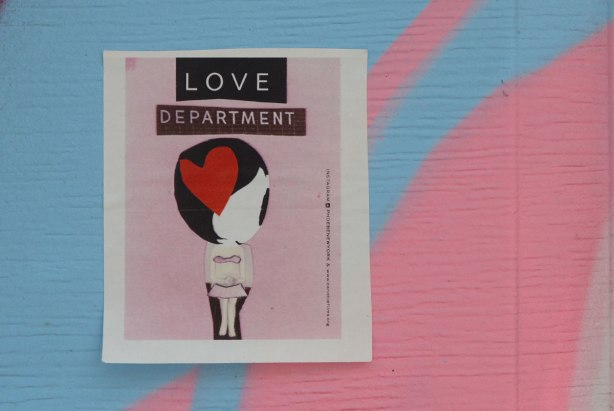 A little paper paste up of a large headed girl with black hair and a large red heart on her head. on a pink background with the words Love Department. Stuck on a garage door painted in pink and blue shapes