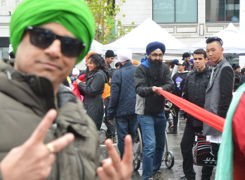 a man in a green turban is close in the foreground and is out of focus. He is wearing sunglasses and is giving the peace sign with both hands