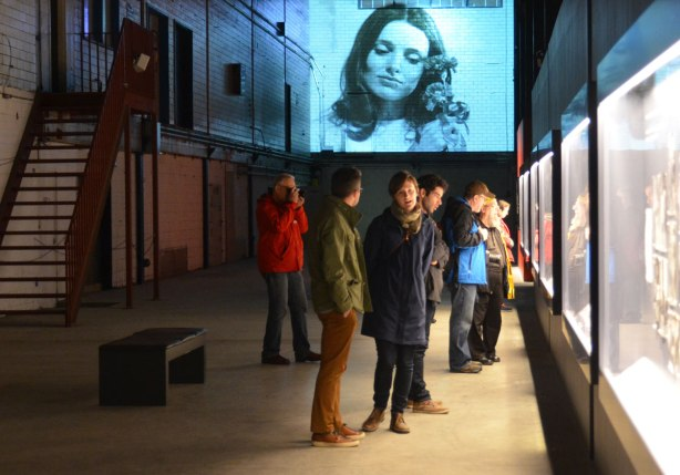 people standing in a large room, the old Press Hall at the Globe and Mail newspaper, looking at an exhibit of old photos. Some photos are being projected onto a wall