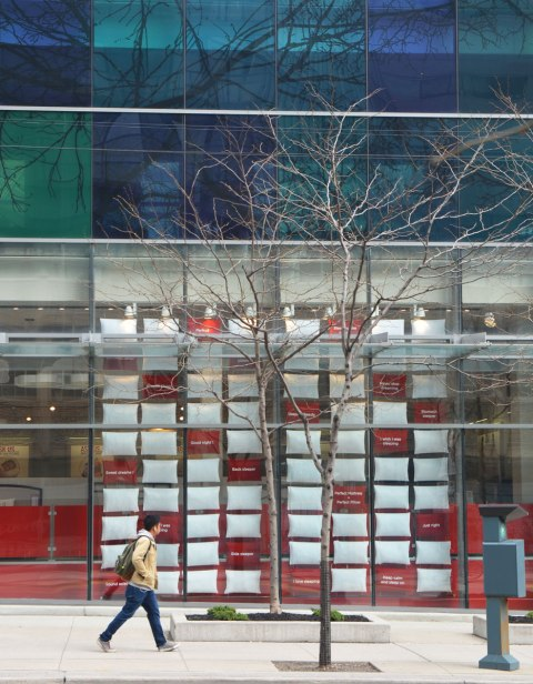 green and blue glass of a building's facade, with a storefront below. The windows of the store are filled with red and white pillows arranged in a grid.