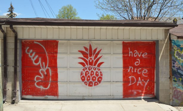 "On a gararge door in a laneway, painted like the Canadian flag except there is a pineapple in the middle instead of a maple leaf. On the right hand side red stripe are the words ""have a nice day"""